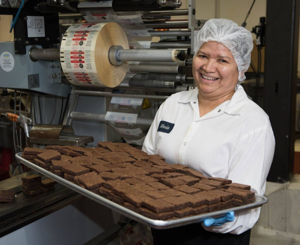 Woman holding a tray of brownies.