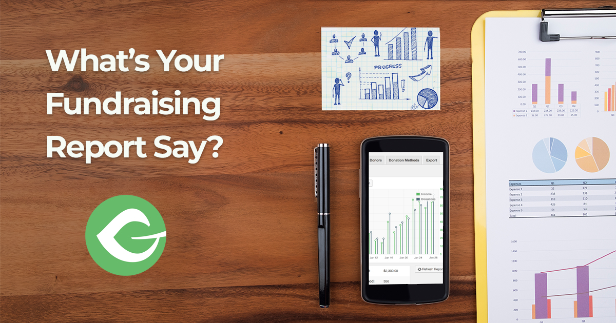 """Charts on a wood desk with the words """"What's Your Fundraising Report Say?"""""""