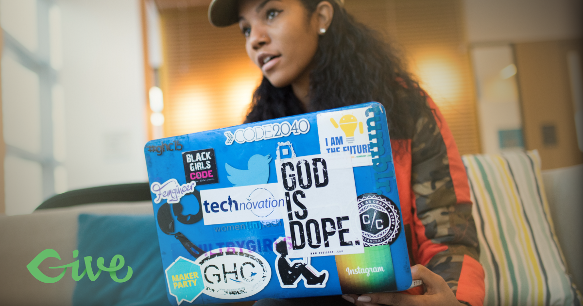 A woman with a laptop with many stickers on it.