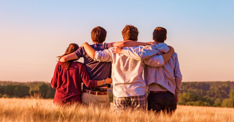 A team of young adults sitting on a grain field watching a lovely sunset