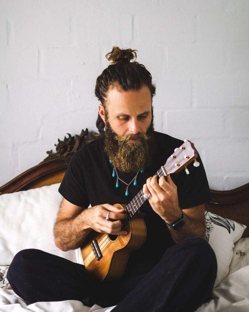 Man with beard playing ukulele.