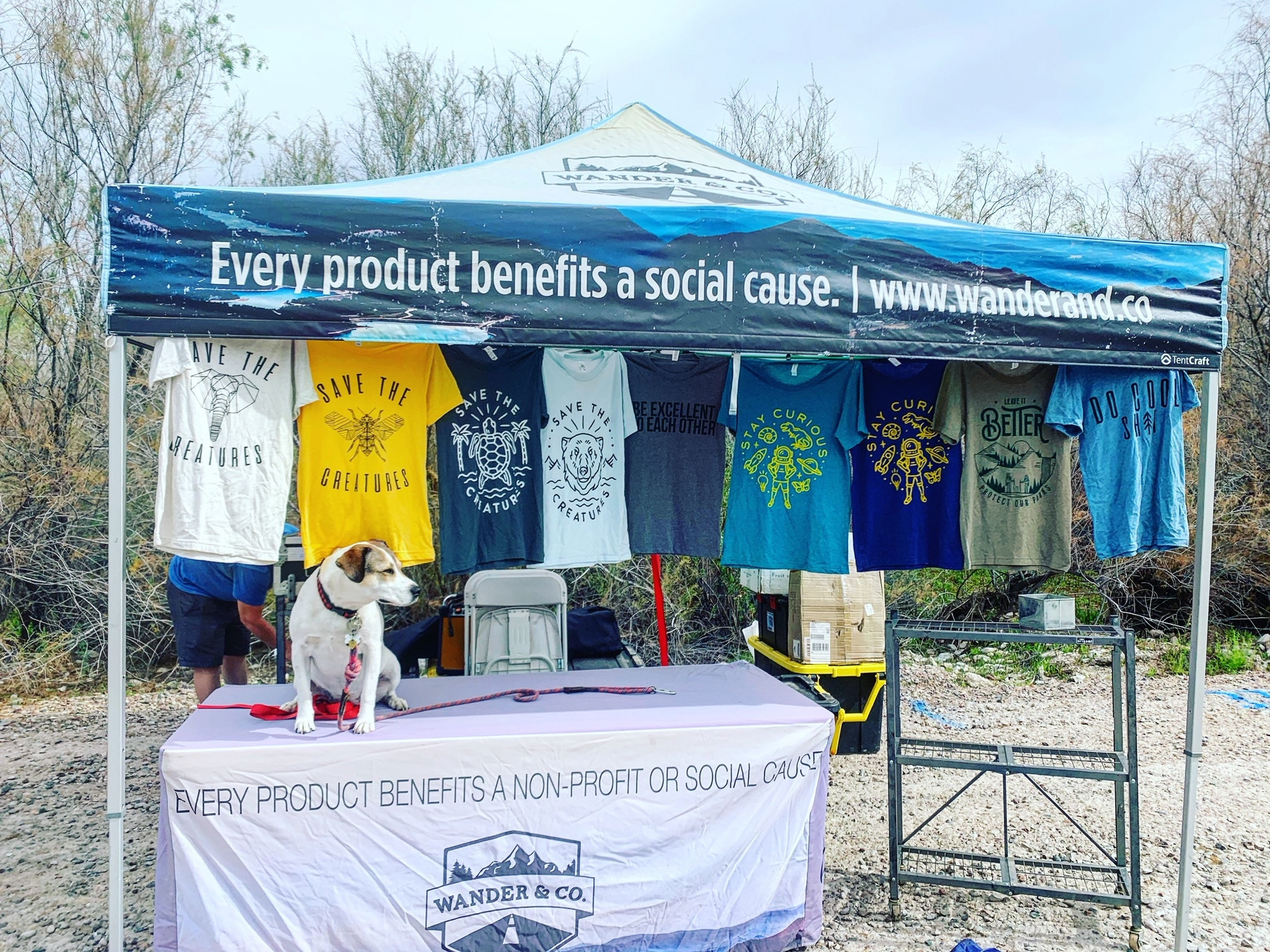 Wander & Company t-shirts hanging at a festival booth.
